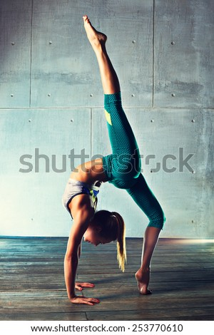 Young slim gymnast woman in sports clothing standing upside down on wall background. - stock photo