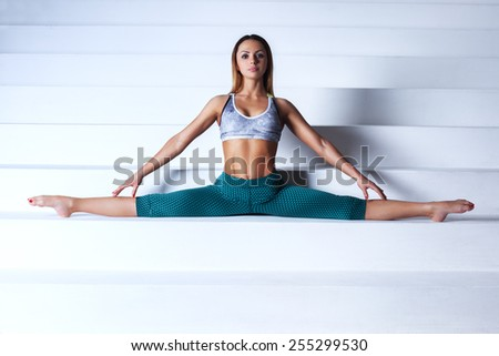 Young slim gymnast woman in sports clothing stretching on bright white stairs. - stock photo