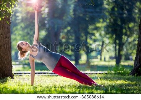 Young slim lady training in the park. Doing yoga exercises on fresh air and enjoying early morning. Healthy lifestyle - stock photo