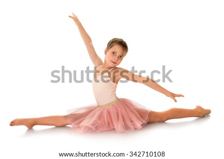 Young slim little ballerina in pink dress sitting on the floor , in the splits - Isolated on white background