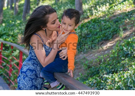 young slim mom with son resting in the Park - stock photo