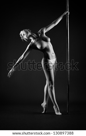 Young slim pole dance topless woman. - stock photo
