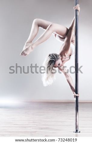 Young slim pole dance woman. Bright white colors. - stock photo