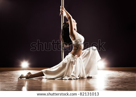 Young slim pole dance woman. Contrast colors. - stock photo