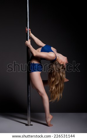 Young slim pole dance woman exercising over dark background - stock photo