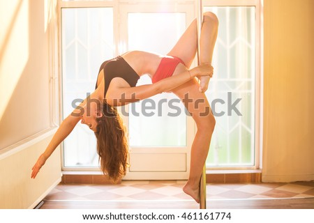 Young slim pole dance woman in dance studio at sunset.