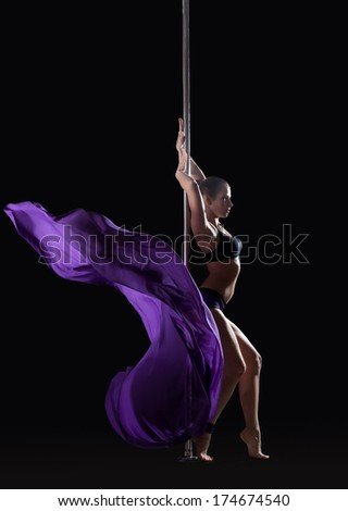 Young slim pole dancer posing with violet cloth