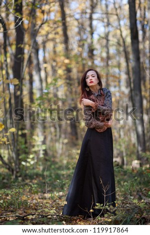Young slim red autumn girl dance in autumn forest