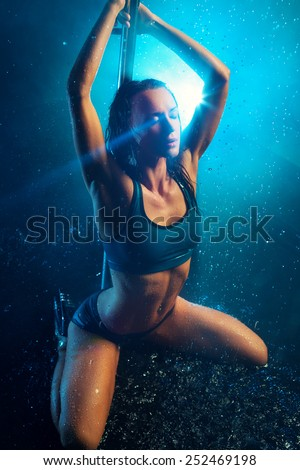 Young slim sexy brunette pole dance woman. Water rain with smoke and blue flare. - stock photo