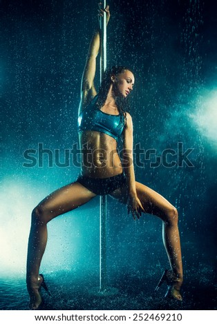 Young slim sexy brunette pole dance woman. Water rain with smoke and flares. - stock photo