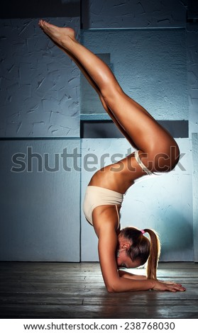 Young slim sexy gymnast woman in lingerie standing upside down on stone wall background. - stock photo