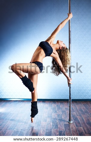 Young slim sexy pole dance woman in black lingerie.