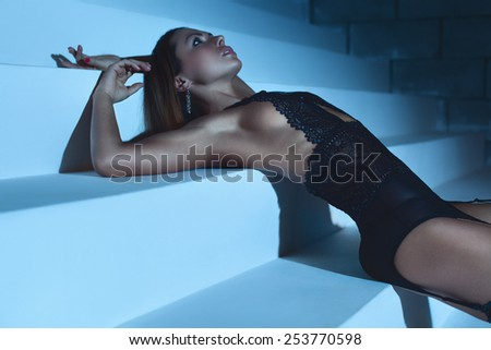 Young slim sexy woman in black lingerie posing on stairs. Soft night blue tint. - stock photo