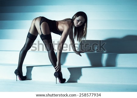 Young slim sexy woman in black lingerie standing on stairs. Soft night blue tint. - stock photo