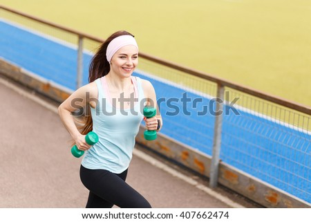 Young slim smiling woman jogging with dumbbells. Sporty happy girl running near a stadium - stock photo
