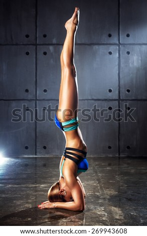 Young slim sports woman standing upside down on wall background. - stock photo