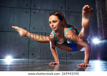 Young slim sports woman stretching in yoga pose. - stock photo