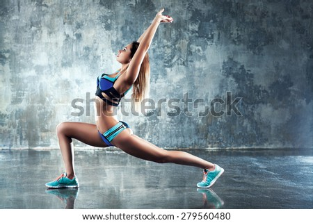 Young slim sports woman stretching on stone wall background. - stock photo