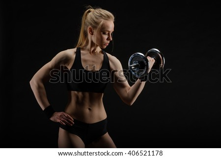 Young slim strong muscular woman posing in studio with dumbbell on black background