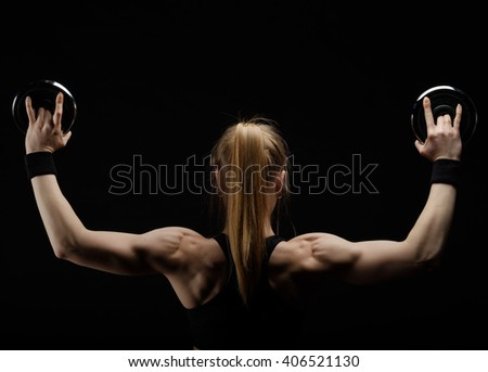 Young slim strong muscular woman posing in studio with dumbbell pancakes on black background - stock photo