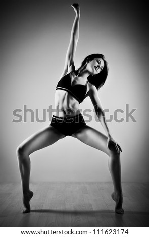 Young slim woman dancing. Black and white.