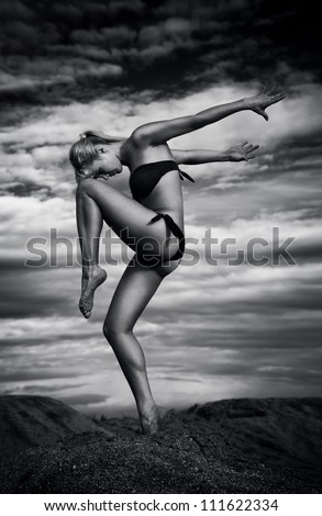 Young slim woman dancing outdoors. Black and white. - stock photo