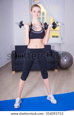 young slim woman doing exercise with dumbbells at home