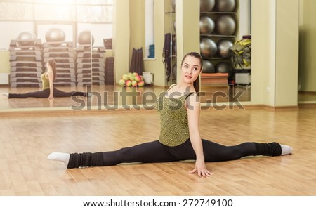 Young slim woman doing front split in fitness class - stock photo