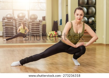 Young slim woman doing stretching in fitness class