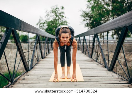 young slim woman doing yoga in the park on the wooden bridge - stock photo