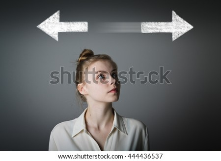 Young slim woman has to decide between two directions. Girl in white full of doubts and hesitation.