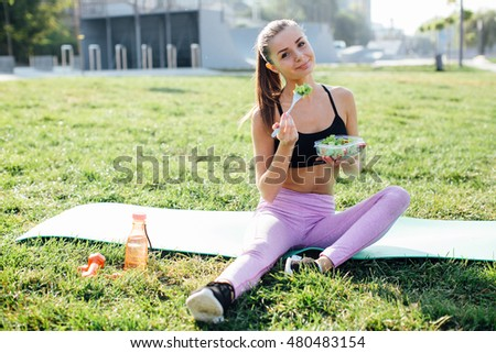 Young slim woman holding a bowl of fresh salad ofter working out outdoors in the park. Eating on fresh air and drinking water, sitting on the grass and enjoying early morning. Healthy lifestyle.