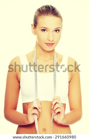 Young slim woman holding measure - stock photo
