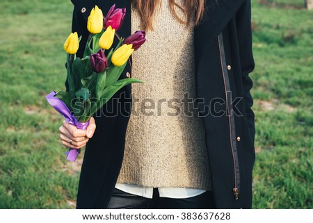 Young slim woman in coat standing on green grass and holding a bouquet of tulips in hand
