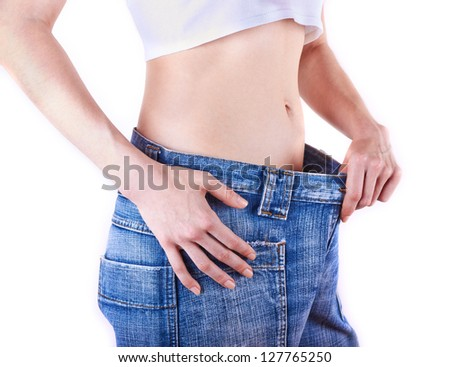 young slim woman in oversized pair of blue jeans over white background