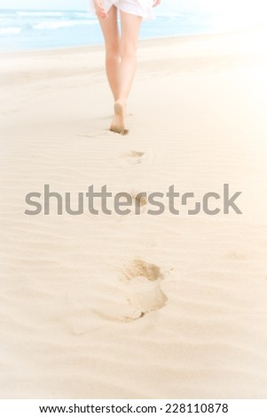 Young slim woman in white swimsuit walking to sea or ocean leaving footprints on soft sand. Blue ocean waves with foam in background. Bathing or sunbathing on beach. Holidays and vacations in summer. - stock photo