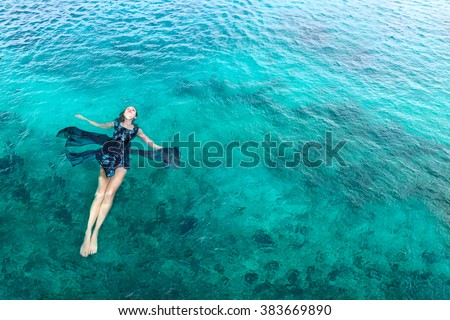 Young slim woman lie on back and relaxing in blue sea water fashion shot - stock photo