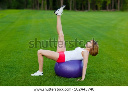 Young slim woman making exercises on fit ball, outdoor - stock photo