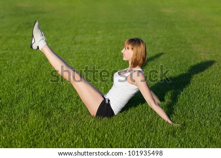 Young slim woman making fitness exercises, outdoor - stock photo