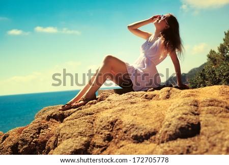 Young slim woman on sea coast. - stock photo