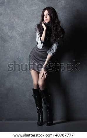 Young slim woman on wall background. - stock photo