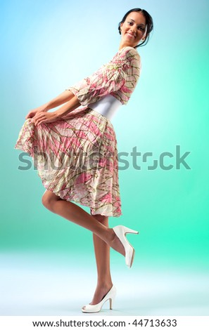 Young slim woman on white-blue-green background. - stock photo