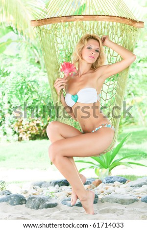 Young slim woman relaxing in hammock outdoor - stock photo