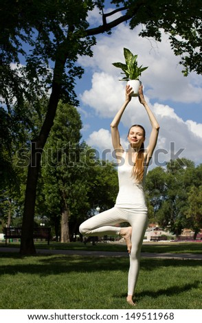 young slim woman standing in yoga  pose in park, holding green flower in pot, near big green tree - stock photo