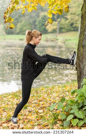 Young slim woman stretching her muscles after running in park - stock photo
