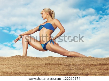 Young slim woman stretching outdoors.