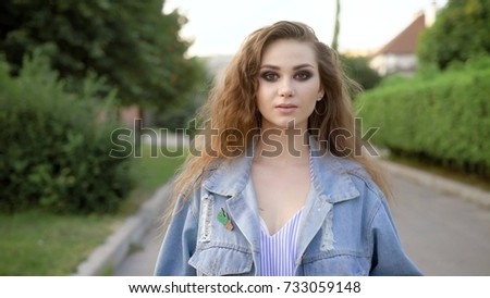 young slim woman with long dark hair and brown eyes is wearing in jeans jacket is walking forward and looking at a camera in sunny summer day.