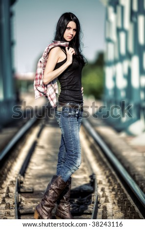 Young slim woman with shirt at the railway. - stock photo