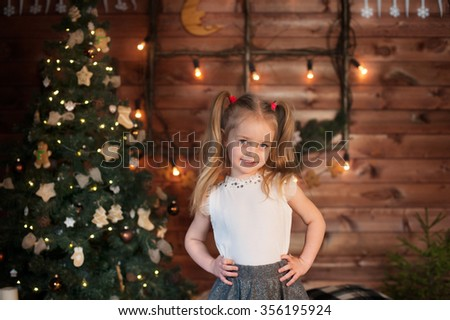 Young sly girl smile near Christmas tree. New Year celebration. - stock photo