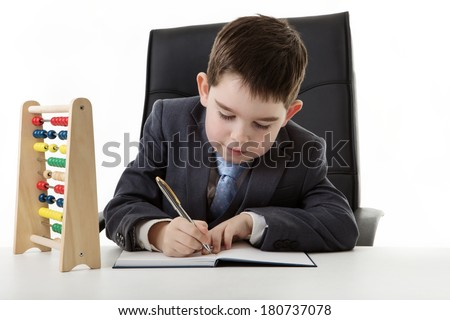 young small boy pretending he's working in an office with a abacus on his desk